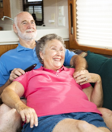Senior couple relaxing together in their travel trailer motor home .   photo