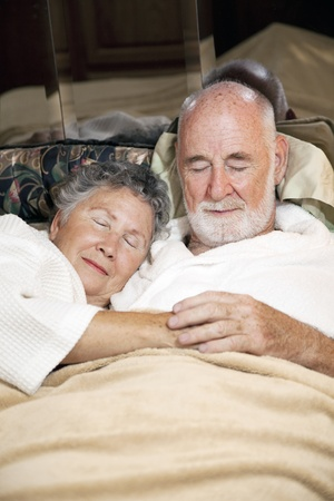 Senior couple asleep in bed, holding hands.  Vertical view.   photo