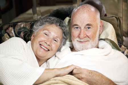 Portrait of loving senior couple in bed together.   photo