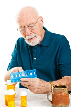 Senior man uses a pill organizer to prepare his medication for the week.  White background. photo
