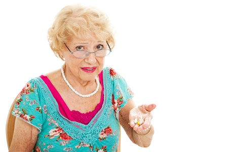 healthcare costs: Senior woman holding a handful of pills and unhappy about taking them.  Isolated on white.