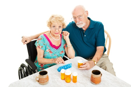 Senior couple frustrated by health issues, sitting at the table surrounded by pill bottles.  Isolated on white.   photo