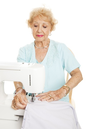 Elderly woman sews with her sewing machine.  Isolated on white.   photo