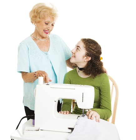 Teenage girl learning to sew with some help from her grandmother.  Isolated on white.   photo