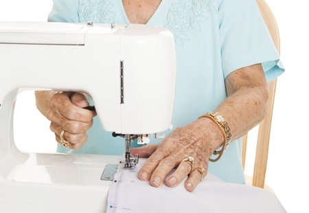 Senior womans hands using her sewing machine. White Background. photo