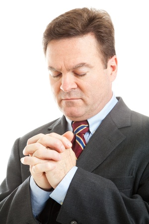 head bowed: Closeup of businessman with his head bowed in prayer.  White background.