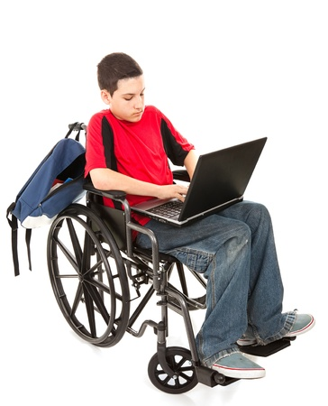 disable: Disabled teen boy using a laptop computer.  Full body isolated on white.