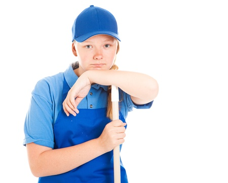 first job: Teenage girl in a work uniform, leaning on a mop or broom handle and looking bored and unhappy.  Isolated on white.