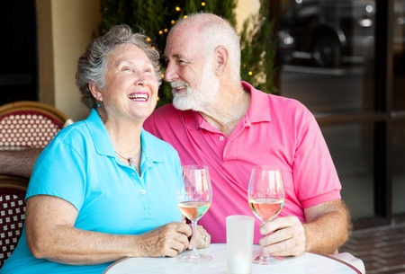 Senior couple at a cafe, enjoying wine and conversation together.   Imagens