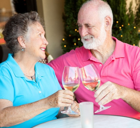 Senior couple at a cafe, enjoying a glass of white wine together.   photo