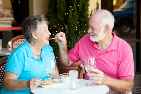 Senior couple on romantic lunch or dinner date.  Hes feeding her the appetizer by hand.   photo