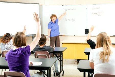 Students raise their hands to solve a problem in algebra class.  photo