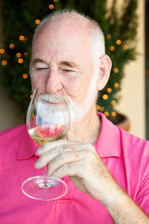 Senior man, enjoying the taste and aroma of a good glass of white wine.   photo