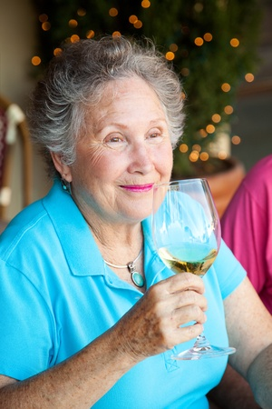 Senior woman enjoys the taste and aroma of a good glass of white wine.   photo
