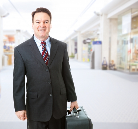 Stock photo of a businessman holding his suitcase and walking through the airport concourse.   photo