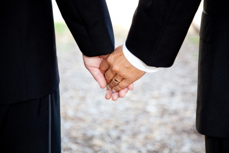 Closeup of a gay couple holding hands, wearing a wedding ring.  Couple is a hispanic man and a caucasian man. photo