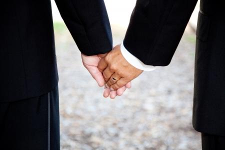 hombres gays: Primer plano de una pareja gay de la mano, que llevaba un anillo de bodas. Pareja es un hombre hispano y un hombre caucásico.