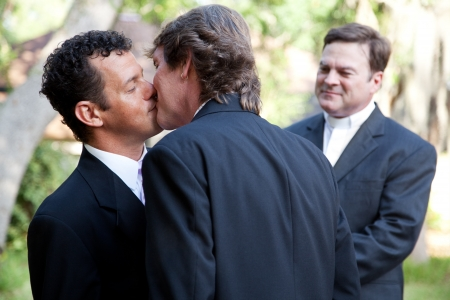 gay love: Wedding of handsome gay male couple.  The grooms kiss as the minister looks on.