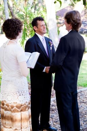 boda gay: Pareja gay diciendo sus votos matrimoniales frente a una ministra mujer joven. Foto de archivo