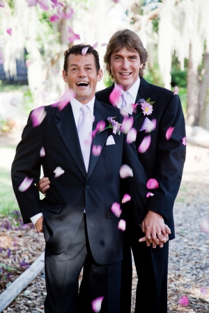 homosexual couple: Gay wedding couple being showered with rose petals.   Stock Photo