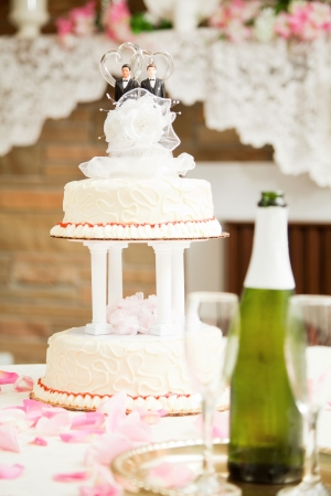 Wedding cake decorated with two grooms, on a reception table with champagne and rose petals. photo