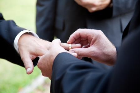 gay couple: One groom placing the ring on another mans finger during gay wedding.   Stock Photo