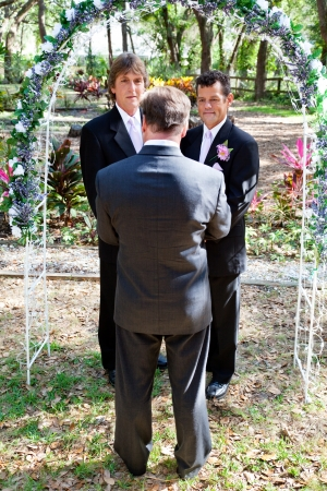 boda gay: Pareja de hombres gay de casarse en un hermoso jardín debajo de un arco de flores.