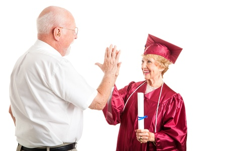 Senior woman graduating from high school gets a high five from her husband.  Isolated on white.   photo