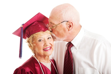 earns: Senior woman earns a college degree and a kiss from her husband.  Isolated on white.   Stock Photo