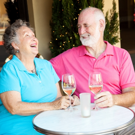 Senior couple on a date, laughing together over wine.   photo
