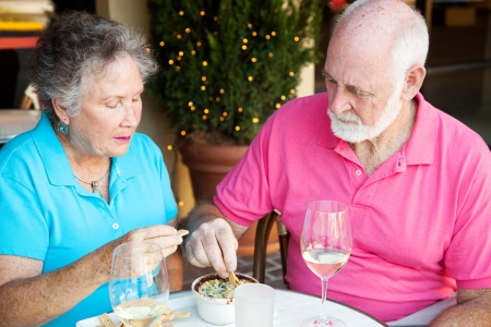 angry couple: Senior couple dining out, looking serious and not very happy.