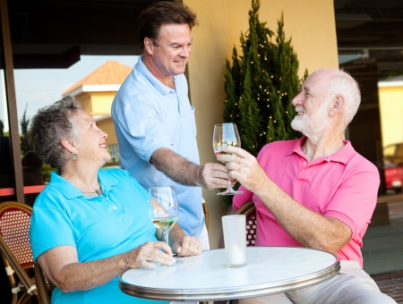 alcohol server: Waiter serving wine to a senior couple at a restaurant.  Stock Photo