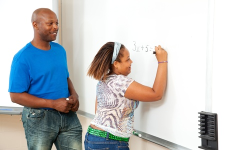 Handsome african-american math teacher works with a student at the board.   photo