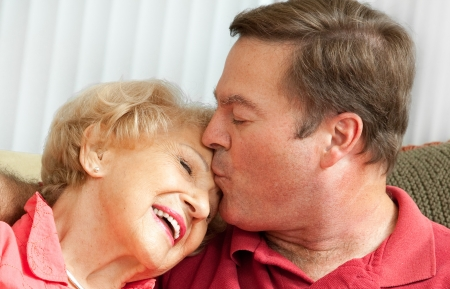 mom kiss son: Adult man kissing his elderly mother on the forehead.  Closeup portrait.