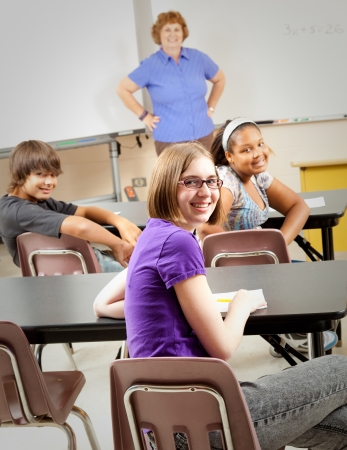 Portrait of teenage students and their teacher in the classroom.  Focus on the girl in the front with glasses. photo