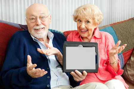 Confused senior couple holding their new tablet PC.  Blank computer screen ready for your text. photo