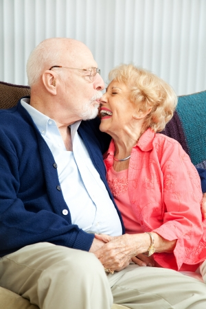 Senior couple relaxing at home, she's laughing as he kisses her nose.   photo