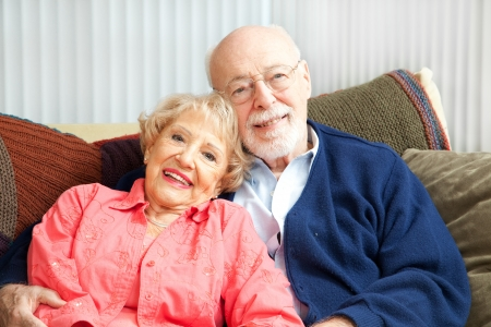 Retired senior couple relaxing together on their living room sofa. Stock Photo - 13982961