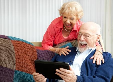 자신의 손자와 함께 화상 채팅에 자신의 태블릿 PC를 사용하는 동안 웃 고 수석 커플. 스톡 콘텐츠