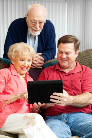 Son teaching his elderly parents how to use a new tablet PC.   Stock Photo - 13982962