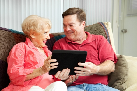 teaching adult: Adult man giving his mother a tablet PC and teaching her to use it.