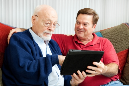 Adult son teaching his father to use a new tablet PC .   版權商用圖片