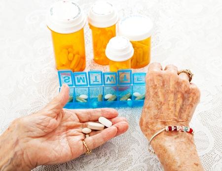 artritis: Primer punto de vista de las manos de un ochenta años de edad senior de la mujer mientras separa la ropa de su medicamento recetado.