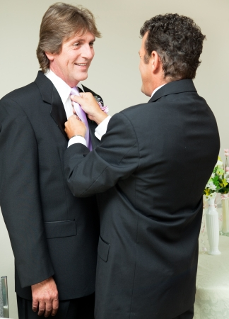 interracial love: One groom straightens the other grooms tie