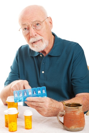 sorting: Confused senior man cant remember whether or not he took his pills.  Could be early sign of Alzheimers Disease or dementia.   Stock Photo