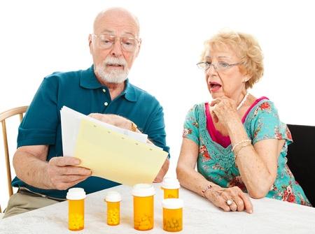 약물 치료: 자신의 의료 법안의 높은 비용에 충격을 수석 커플. 흰색 배경입니다.
