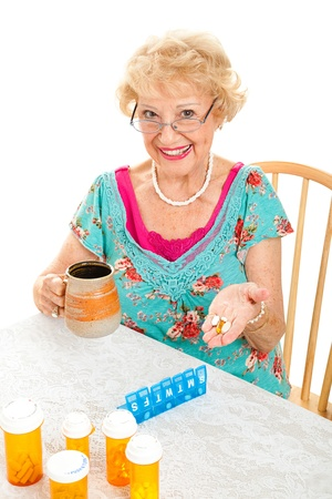 Smiling senior lady cheerfully takes her prescriptions and suppliments.  White background.   photo