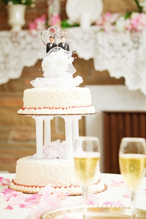 topper: Wedding cake with two grooms on top, for gay marriage ceremony.   Stock Photo