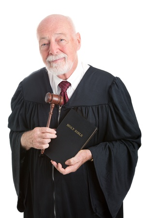 Judge holding his gavel and a bible   Metaphor for balancing church and state   Isolated on white    photo