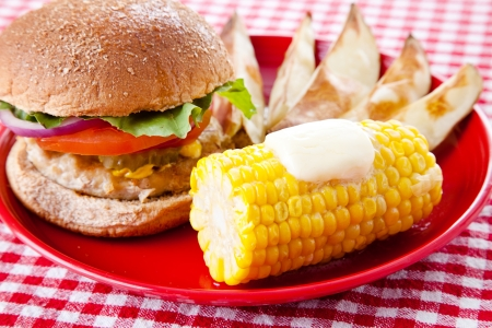 Healthy turkey burger on whole grain bun, with baked potato wedges and corn on the cob  Low fat picnic options    photo
